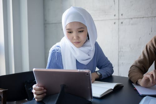 Concentrated Muslim female student in headscarf surfing tablet while sitting at table with copybook during lesson in university lecture room