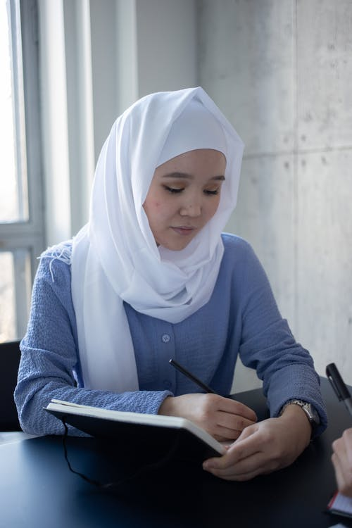 Attentive Asian woman in hijab writing in copybook during studies