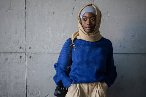Content Muslim female student in traditional headscarf wearing blue sweater looking away while standing near wall with backpack in corridor of university