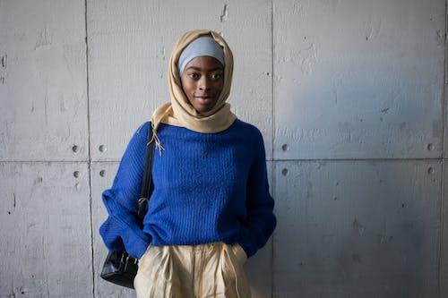 Cheerful black woman in hijab near wall
