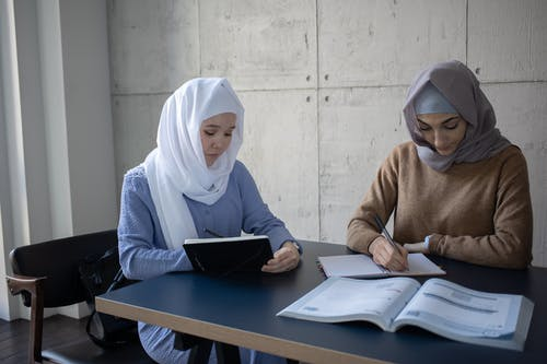 Concentrated multiracial female students in headscarves taking notes in workbooks  while sitting at table with textbook during lesson preparation in university