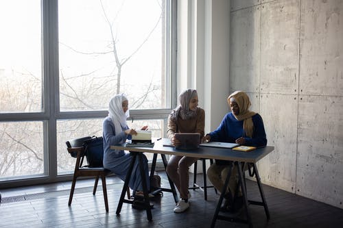 Diverse Muslim businesswomen talking about job at table with tablet