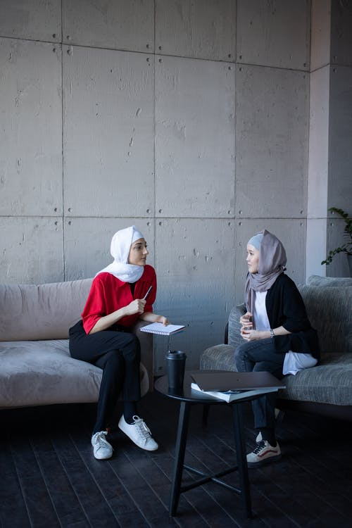 Islamic multiethnic women in headscarves discussing plan of job together in comfortable workplace in daytime