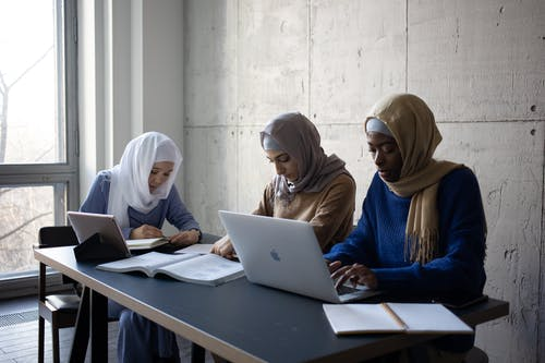 Serious young multiethnic Islamic female students in casual clothes and hijab sitting at table while surfing on netbooks and taking notes in notepads near textbook in light room near window