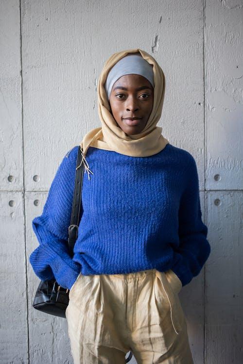 Islamic African American female in hijab and bag near wall