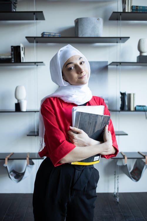 Muslim female with notebooks in apartment near shelves with decorations