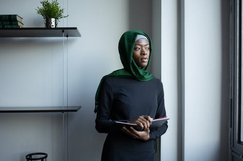 Thoughtful black Muslim lady in hijab standing with notebook