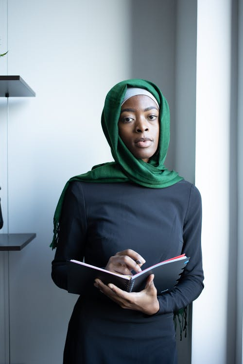 Confident young African American Islamic woman wearing black dress and hijab while standing with notepad in light room near shelves and looking at camera