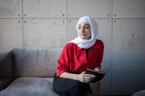 Dreamy Muslim female with notebook on couch in room