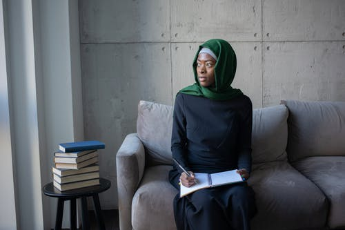 Thoughtful young black Muslim lady wearing elegant dress and hijab while sitting on gray soft couch with notepad and pen near table with books in bright room while looking away