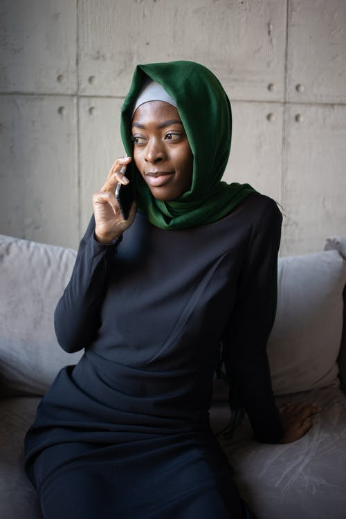 Black Muslim lady in hijab speaking on cellphone on couch
