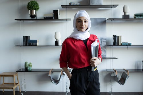 Confident young Muslim lady in hijab and casual outfit standing in light apartment with notebooks near shelves with different decorative objects and small wooden stand while looking at camera