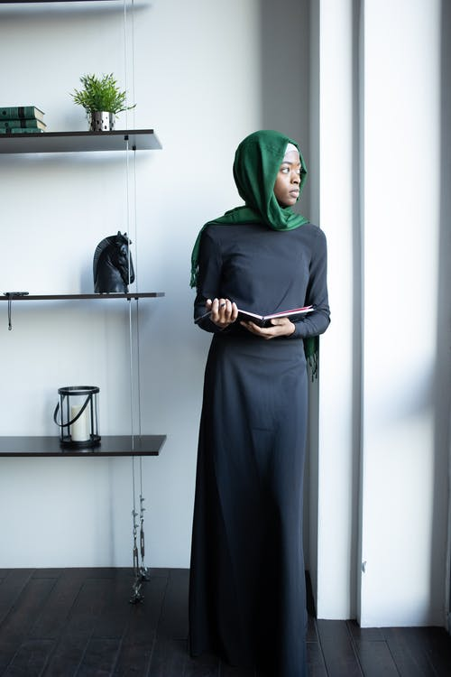 Islamic African American female in hijab with notepad in office
