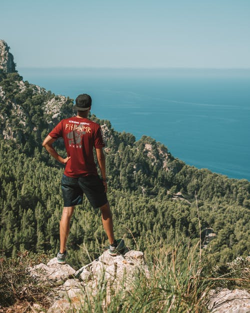 Man in Red T-shirt and Black Shorts Standing on Rock Formation Looking at the Sea