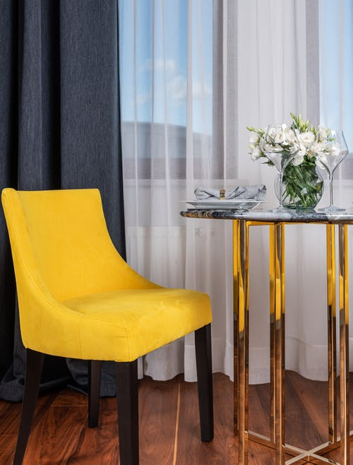 Modern living room interior design with comfy stylish yellow chair and glass coffee table near window