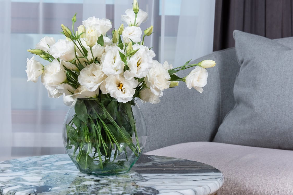 Bunch of fresh delicate white lisianthus flowers placed in glass vase arranged on round marble table near comfortable sofa in elegant apartment