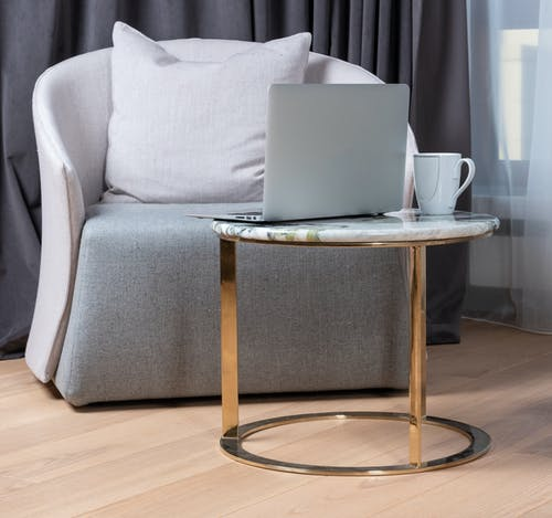 Modern laptop and cup of coffee placed on small round marble table near comfortable armchair during remote work at home