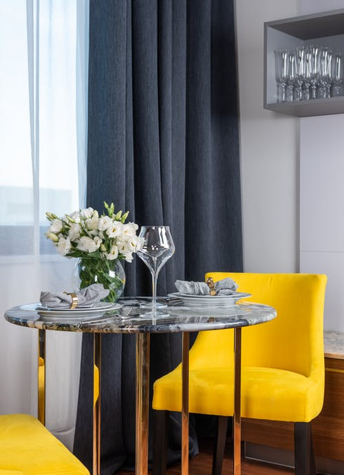 Elegant table setting and yellow chairs in modern apartment