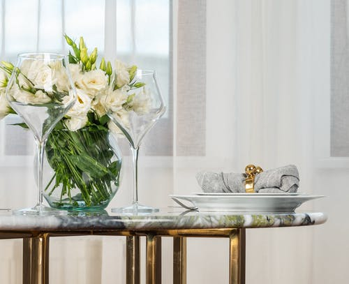 Pair of elegant wineglasses and white plate with napkin with golden ring served on marble table with bunch of fresh white lisianthus flowers in vase in modern restaurant