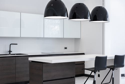 Interior of modern kitchen with minimalist furniture and creative lamps hanging above counter and bar chairs