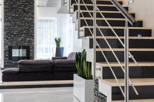 Modern house with staircase and cozy sofa decorated with exotic houseplants