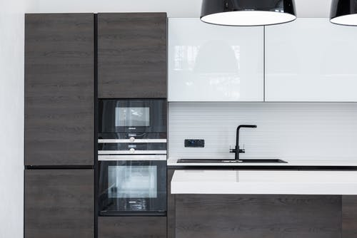 Interior detail of modern kitchen with minimalist furniture contemporary appliances decorated with lamps hanging over counter