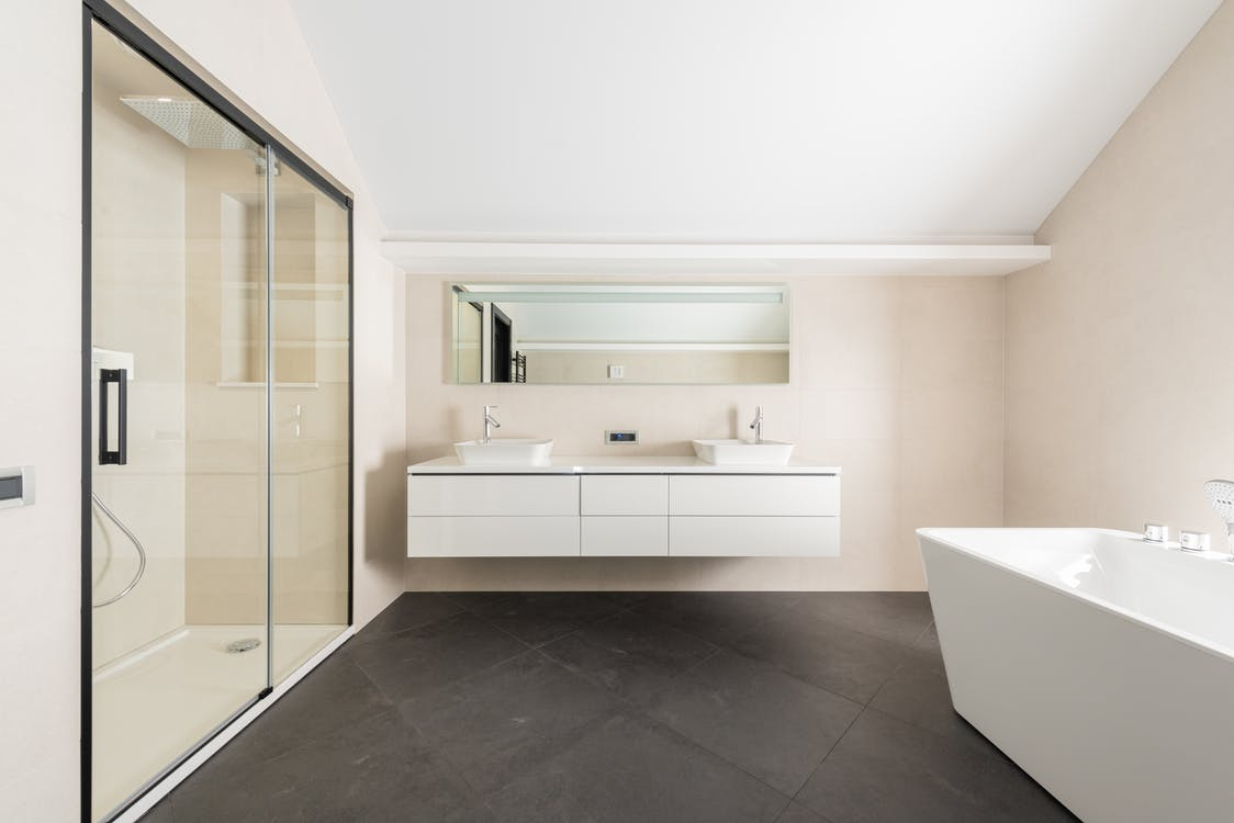 Interior of spacious modern bathroom with shower cabin bathtub and minimalist furniture in contemporary apartment