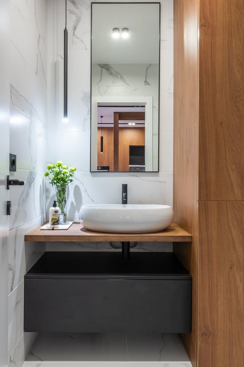 White ceramic sink and mirror in modern bathroom with wooden furniture and marble walls