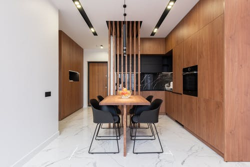 Stylish kitchen with wooden furniture and dining zone