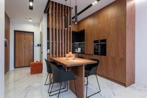 Dining area in modern kitchen with stylish wooden furniture and appliances decorated with creative lamps