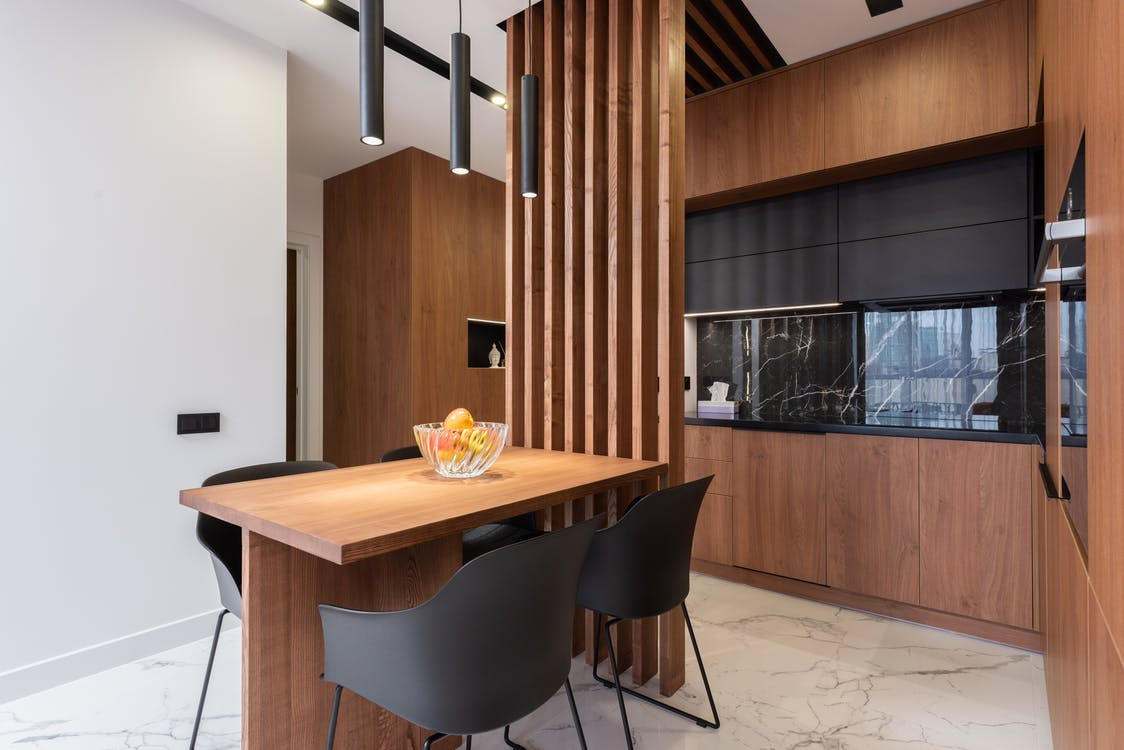 Interior of contemporary kitchen with wooden table and furniture in modern apartment