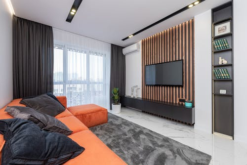 Modern spacious room with window and black cushions on orange couch placed on rug against wall with striped decorations and TV