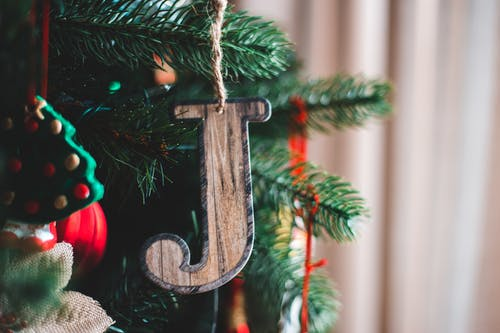 Wooden letter with rope hanging on coniferous tree sprig during New Year holiday in house