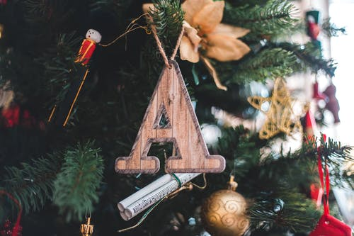 Wooden A letter toy and various creative baubles hanging on Christmas tree branches in daylight