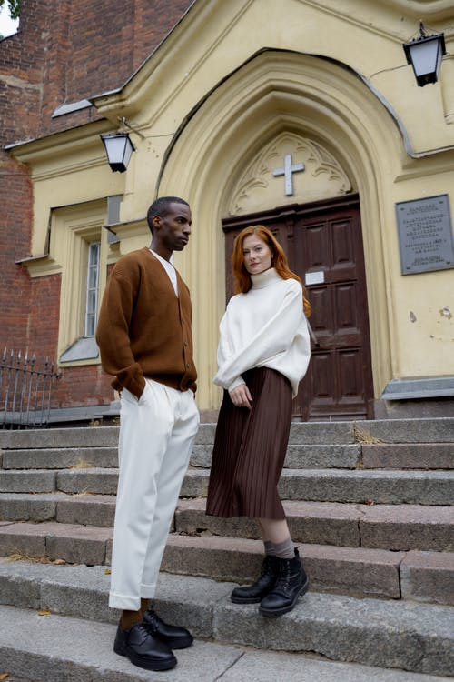Man in Brown Long Sleeve Shirt and White Pants Standing on Brown Brick Wall