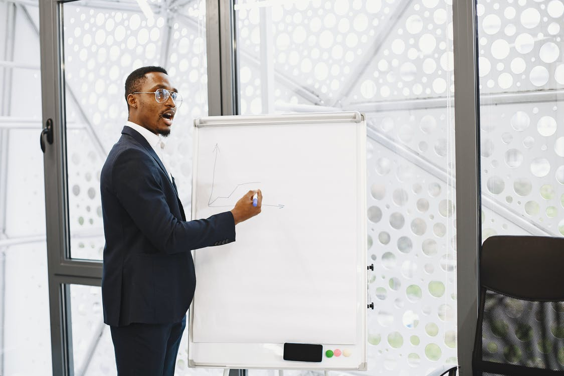 Man in Black Suit Standing in Front of White Board