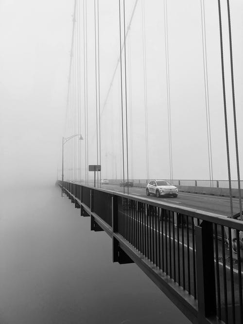 Grayscale Photo of Vehicles Traveling on Cable-Stayed Bridge during Foggy Weather