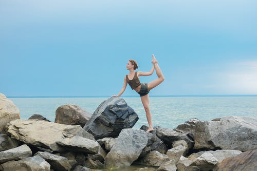Female stretching legs on rocks near water