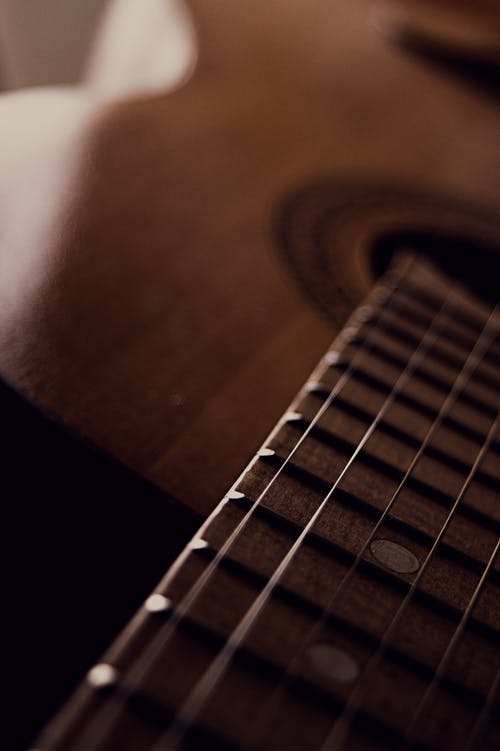 Selective Focus Photo of a Brown Acoustic Guitar