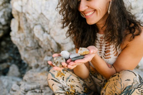 拿着灰色石头的棕色和白色花卉长袖衬衫的女人