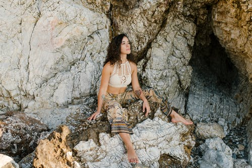 Young woman in summer outfit relaxing on stones in mountain terrain