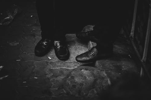 Black and white of crop unrecognizable males in trousers and trendy boots standing on street