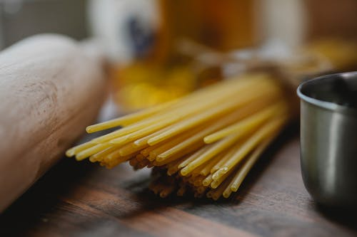 Bunch of uncooked spaghetti near metal bowl and rolling pin placed on wooden surface on light kitchen