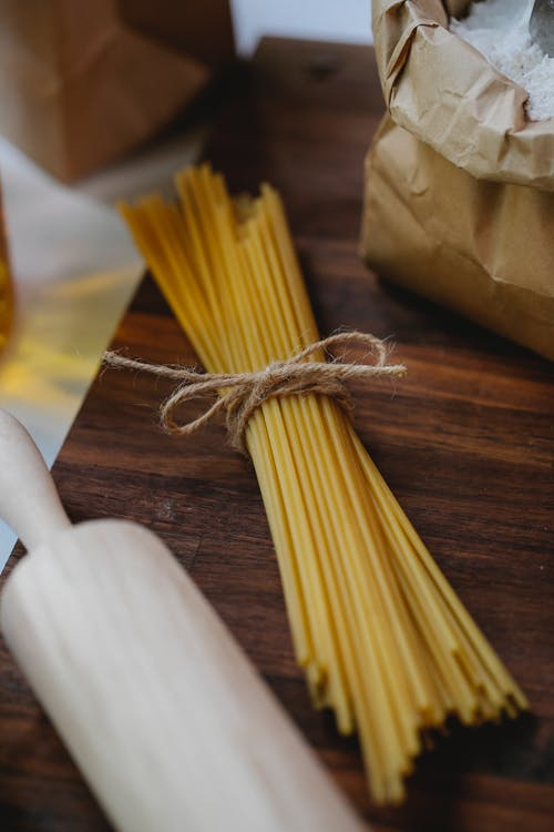 Spaghetti and rolling pin near flour on wooden surface