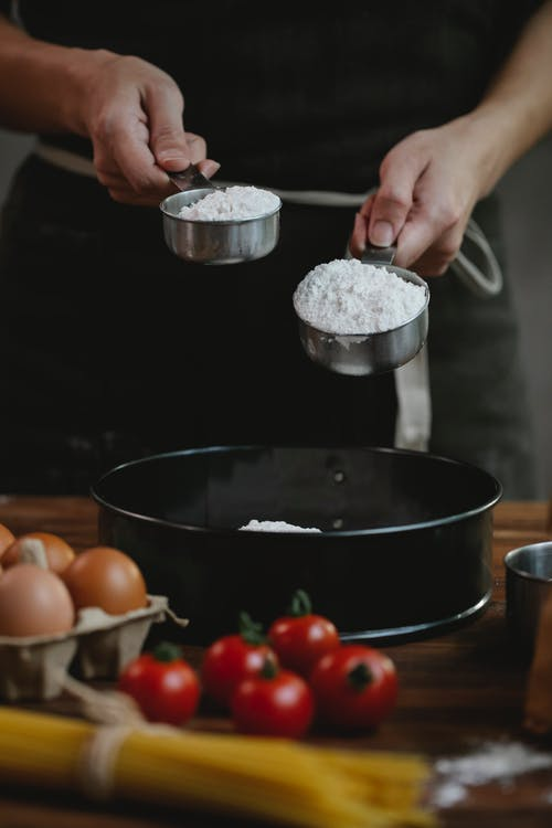 Crop unrecognizable chef in black apron standing near table and adding flour in dishware while cooking homemade pasta with eggs and spaghetti near tomatoes