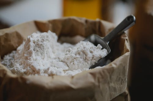 Paper bag of wheat flour with stainless scoop