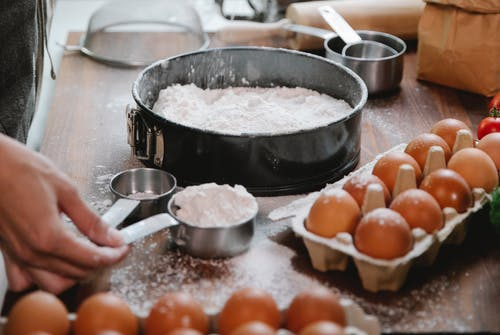 High angle of crop anonymous cook adding flour into baking dish while preparing pastry in kitchen