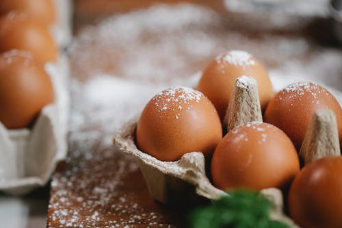 Eggs in carton container on table with flour