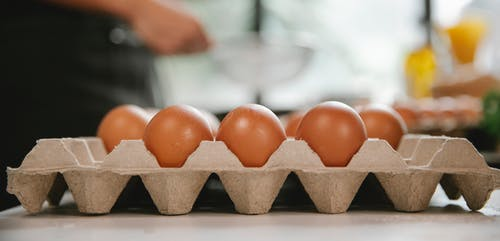 Eggs in carton container placed on table near chef cooking food in kitchen