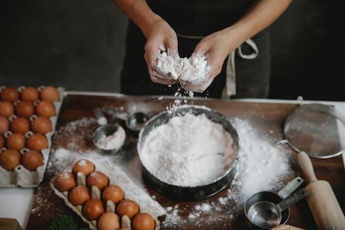 Cook adding flour to recipe of dough